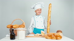 Young baker girl child holds long loaf and smiling at camera standing Stock Footage