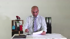 Bald bureaucrat sitting at desk in office stamping paperworks Stock Footage
