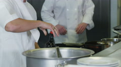 4K Happy trainee chef pouring wine into a dish in a professional kitchen Stock Footage