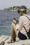 Woman in cap and with backpack is seating near of the sea and watching someth Stock Photos