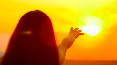 The girl pulls a hand to the gold sun Stock Footage