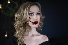 Beautiful young blonde woman in black dress with halloween make up a Stock Photos