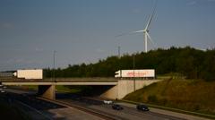 Time lapse traffic passing electricity generating windmills motorway leeds uk Stock Footage