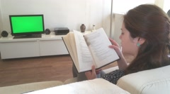 Charming Young Woman Reading And Watching TV, Green Screen Stock Footage