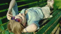 Pretty girl lying on the wooden bench and relaxing Stock Footage