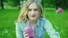 Pretty girl smiling to the camera and drinking fruity cocktail, steadycam shot Stock Footage