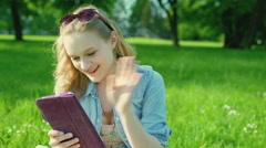 Pretty girl sitting on the meadow and having videocall on tablet, steadycam shot Stock Footage