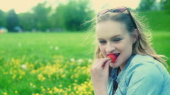 Pretty girl eating strawberry and smiling to the camera on the meadow Stock Footage