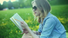 Absorbed girl reading book and studying while sitting on the meadow Stock Footage