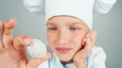 Extreme close up portrait chef cook holds playing with quail egg Stock Footage
