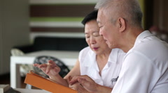Asian senior couple reading news together from tablet in small library Stock Footage