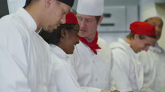4K Happy team of chefs in a commercial kitchen, head chef tastes Arkistovideo
