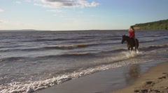 Woman riding on horse at river beach in water sunset light Stock Footage