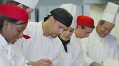 4K Happy team of chefs in a commercial kitchen, head chef tastes Stock Footage