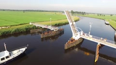 Pleasure boat passes through open bridge typical Dutch landscape. Stock Footage