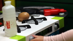 Close up girl playing a toy kitchen Stock Footage