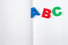Lined exercise book and ABC letters - stock photo