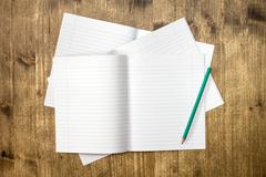 Lined exercise books and pencil Stock Photos