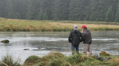 Mature man teaching young man to fly fish on Alaskan river Stock Footage