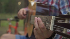 Young man in sun park holding a guitar and playing music Stock Footage