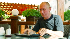 4K.  Adult man    in street café works at  laptop. Modern life Stock Footage