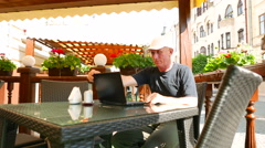 4K.  Adult man    in street café works at  laptop and smile.  Stock Footage