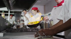 4K Team of professional chefs preparing and cooking food in a commercial Stock Footage