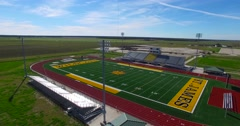 Excellent aerial over a modern high school football stadium in the flatlands of Stock Footage