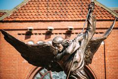 Statue Of Archangel Michael near Red Catholic Church Of St. Simon And St. Helena Stock Photos