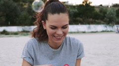 Beautiful young happy woman blowing bubbles on a beach Stock Footage
