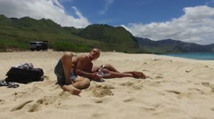 Aerial Man and woman relaxing on the beach, Hawaii Stock Footage