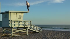 Extreme jump with the rescue tower on the beach, slow motion Stock Footage