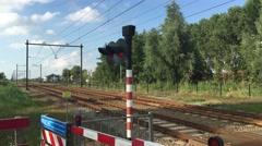 Yellow Dutch train passing by a crossing Stock Footage