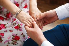 Husband holding hands of his pregnant wife, closeup Stock Photos