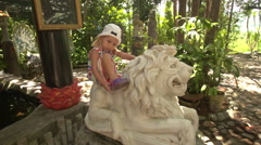 Small Girl Sits on Lion Sculpture in Buddhist Temple Park Stock Footage