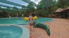 Little Girl Sits down on Toy Crocodile by Pool at Hotel Stock Footage