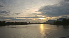 View of Tranquil River with Woody Banks from Bridge at Sunset Stock Footage