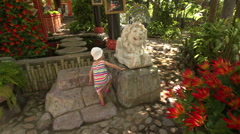 Small Girl Climbs on Lion Sculpture in Buddhist Temple Stock Footage