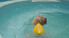 Little Blond Girl in Yellow Arm-bands Swims in Pool at Hotel Stock Footage