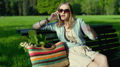 Pretty girl quarrelling while talking on cellphone in the park Stock Footage