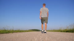 Young Man Going on Countryside Road against Blue Sky Stock Footage