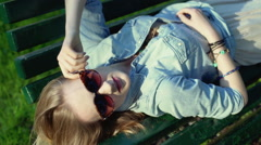 Girl lying on the bench in the park and looking to the camera Stock Footage