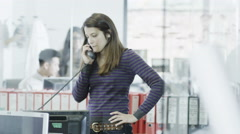 Casually dressed young professional woman takes a call Stock Footage