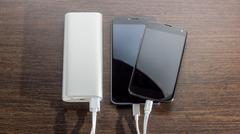 Power Bank charging two smartphones - dark wooden background Stock Photos