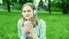 Girl in headphones drinking fruity cocktail while sitting on the meadow Stock Footage