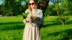 Happy girl standing next to the tree and holding bunch of flowers, steadycam sho Stock Footage