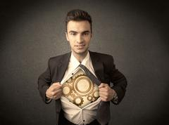 Businessman tearing shirt off and machine cog wheel shows Stock Photos