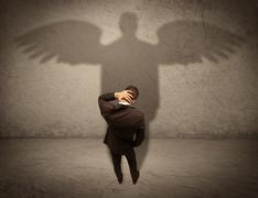 Honest salesman with angel shadow concept Stock Photos