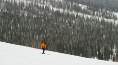 Skier on the slope at a ski resort in the mountains in slowmotion during Stock Footage