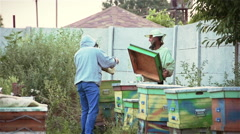 Two beekeepers cover the hive with the bees Stock Footage